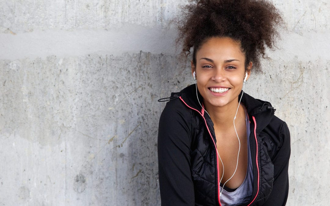Cheerful Young Woman Listening To Music With Earphones